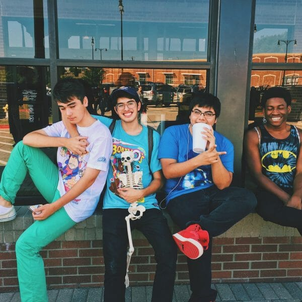 Four teens sitting on window sill